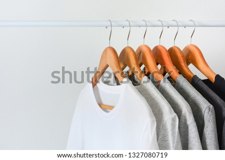 close up collection of black, gray and white color (monochrome) t-shirt hanging on wooden clothes hanger in closet or clothing rack over white background, copy space #1327080719
