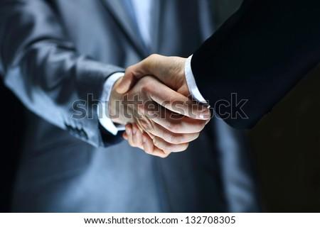 Handshake - Hand holding on black background Royalty-Free Stock Photo #132708305