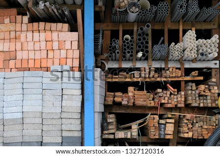 Construction building materials and industrial supplies such as bricks, woods and pipes stacked and arranged for sale at a hardware store front. Royalty-Free Stock Photo #1327120316