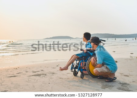 Asian special child on wheelchair and his dad on the beach at sunset, Father helped him to get closer to nature, Life in the education age of disabled children, Happy disabled kid concept. #1327128977