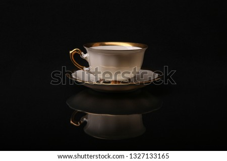 vintage tea set on a black background. retro cup and saucer. white porcelain cup with gold plated close-up. classic cup and saucer from the tea set. old cup and saucer reflected on black background. #1327133165