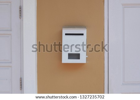 White mailbox between part of white door and window on brown painted wall of house, home exterior decoration concept  #1327235702