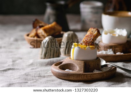Breakfast with cup of coffee and soft boiled egg, served in wooden egg cup with salt, pepper and toasted bread, jug of cream over linen tablecloth. #1327303220