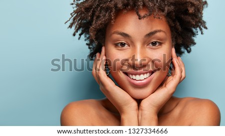 Close up portrait of relaxed black woman has gentle skin after taking shower, satisfied with new lotion, has no makeup, smiles tenderly, shows perfect teeth, stands shirtless against blue background #1327334666