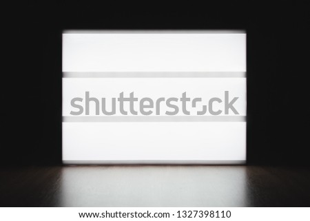 Mock up lightbox luminous display without letters on the table in the dark. Place for text or your design