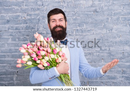 Spring everywhere. Womens day. Flower for March 8. Spring gift. Bearded man hipster love flowers. Bearded man with tulip bouquet. Love date. international holiday. Love spring. Love is in the air. #1327443719
