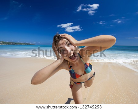 Beautiful and happy young woman  enjoying the summer on a tropical beach