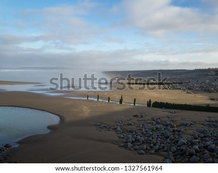 Westward Ho , sand banks , beach groynes and the wonderful natural pebbles in Devon , England Royalty-Free Stock Photo #1327561964
