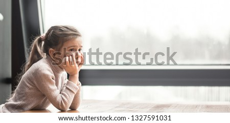 Charming little girl sitting at a wooden table by the window. Upset child #1327591031