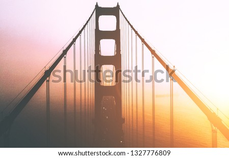 Beautiful Aerial view silhouette of famous San Francisco landmark with name Golden Gate bridge. Scenery bridge tower construction in misty foggy sunset light. Famous California sight in gold sundown #1327776809