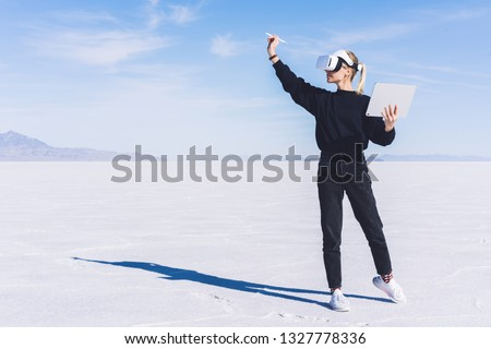 Young female extend hand with digital pencil for interactive touch over air while standing in spacious clear futuristic space wearing virtual reality headset.Hipster girl designing architectural space #1327778336