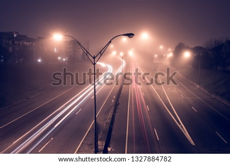 Highway at foggy night with bright trails of light from incoming and outgoing traffic. Transportation, traffic, urbanism and infrastructure concepts. #1327884782