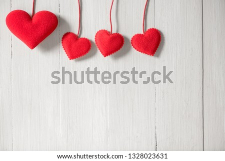 rows of red heart hanging on white wood wall background #1328023631