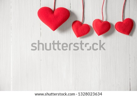 rows of red heart hanging on white wood wall background #1328023634