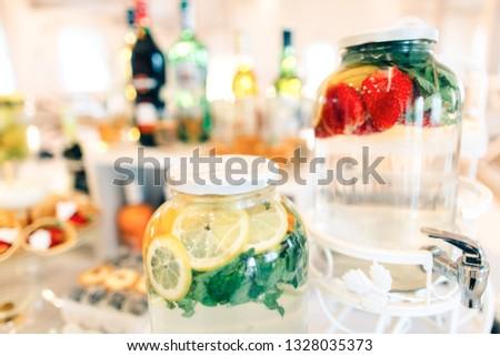 Beautiful handmade fresh lemonade bottles on a wedding table close up #1328035373