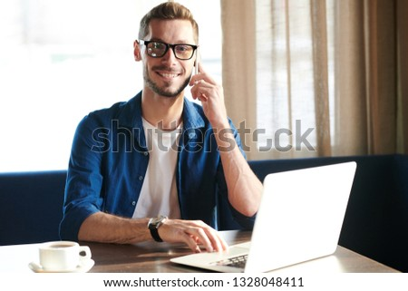 Young successful employee with toothy smile talking on the phone and browsing in the net by workplace #1328048411