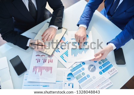 Overview of two businessmen discussing financial papers by desk while organizing work and analyzing statistics Royalty-Free Stock Photo #1328048843