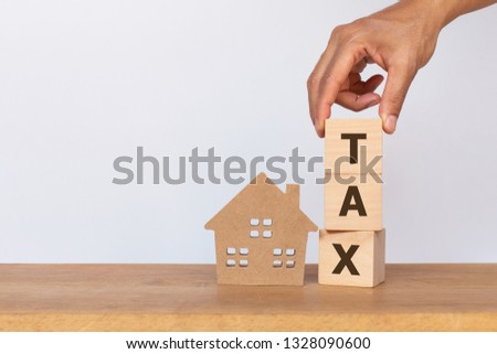 House model and wooden cubes with alphabet TAX on wooden table. Home taxes decrease concept #1328090600
