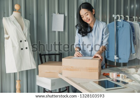 Young business woman working online e-commerce shopping at her shop. Young woman seller prepare parcel box of product for deliver to customer. Online selling, e-commerce. #1328103593