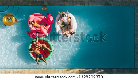 Aerial view of young people on summer vacation enjoying on fun inflatable floats in swimming pool. Group of friends relaxing on air mattresses in pool. #1328209370