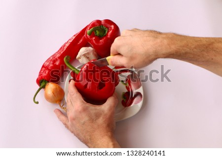 Close-up . Cook hands cutting up a salad of pepper, onion and garlic on a white background. #1328240141