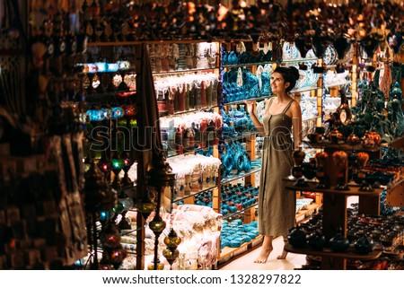 Beautiful girl in a souvenir shop in Turkey. Girl chooses a souvenir Oriental shop. Street shop. Turkish Souvenirs. Oriental bazaar. Turkish Bazaar. Tourist shop. Moroccan Bazaar.  #1328297822