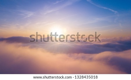 Beautiful sunset cloudy sky from aerial view. Airplane view above clouds #1328435018
