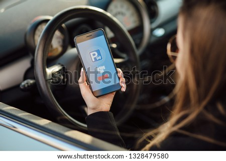Business woman in car. Girl using smartphone app to pay for the parking. #1328479580