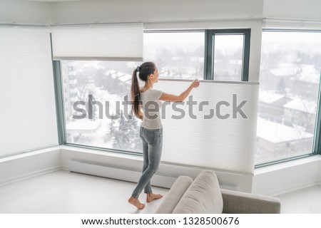 Woman opening home curtains in urban condo. Modern top down bottom up privacy cellular shades on apartment window keeping heat in winter with honeycomb blind curtain. Cordless pleated shades. Royalty-Free Stock Photo #1328500676