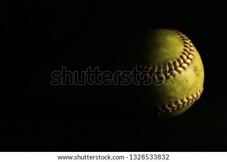 Yellow softball on black background.