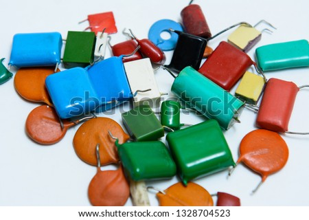 Different type capacitors in different colors. Ceramic,metal, film capacitors. Green,blue,red film capacitors, orange ceramic capacitors. On white background #1328704523