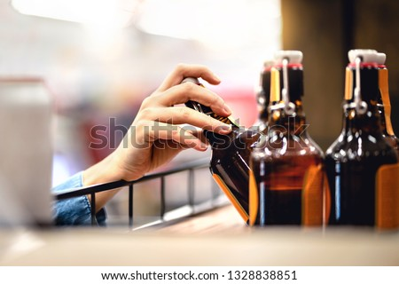 Hand taking bottle of beer from shelf in alcohol and liquor store. Customer buying cider or supermarket staff filling and stocking shelves. Retail worker working. Woman choosing lager or pale ale #1328838851