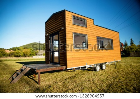 Mobile tiny house. Great for outdoor experiences and wildlife. Lots of mobility and pure adventure. No need for special authorizations, only a decent car to pull this tiny house and off you go. Royalty-Free Stock Photo #1328904557