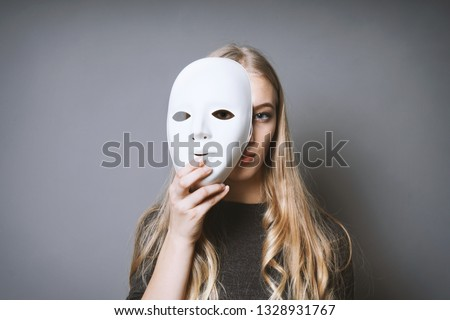 teen girl hiding her face behind mask - identity or personality concept Royalty-Free Stock Photo #1328931767