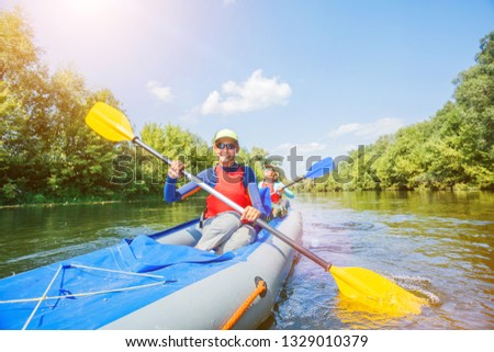 Happy family kayaking on the river. Active girl with her mother having fun enjoying adventurous experience with kayak on a sunny day during summer vacation #1329010379