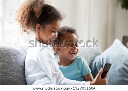 Excited small black brother and sister laugh watching funny cartoon on smartphone, smiling little mixed race siblings have fun using cellphone play game or make selfie. Kids and technology concept