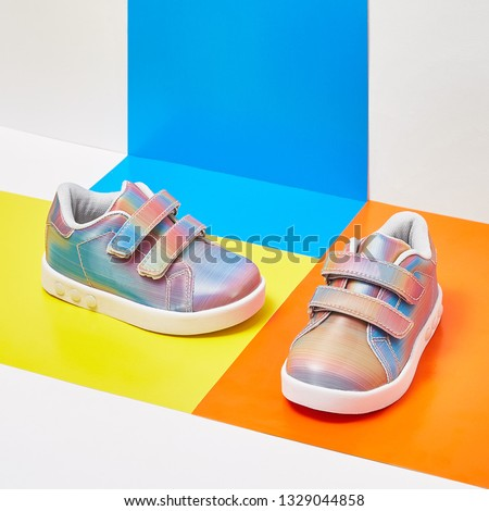 pair of baby shoes on colour background #1329044858