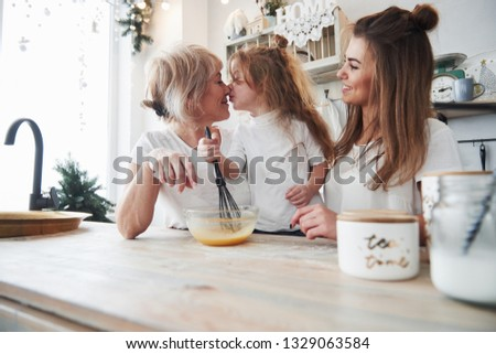 Give me kiss. Mother, grandmother and daughter having good time in the kitchen. #1329063584