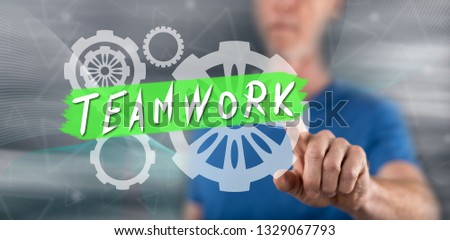 Man touching a teamwork concept on a touch screen with his finger #1329067793