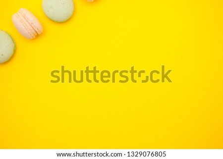 Top view of colorful macaron or macaroon on yellow background. Sweet snack #1329076805