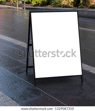 Blank white sandwich sign outside in daytime on dark wet sidewalk
