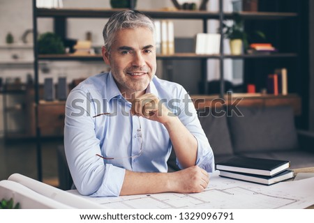 Mature architect working with drawings in office #1329096791