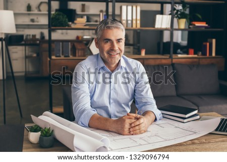Mature architect working with drawings in office #1329096794