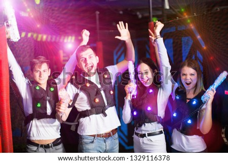 Portrait of cheerful young friends with laser guns in colored beams during laser tag game in dark room #1329116378