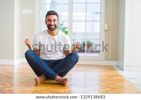 Handsome hispanic man wearing casual t-shirt sitting on the floor at home celebrating surprised and amazed for success with arms raised and open eyes. Winner concept. #1329138683