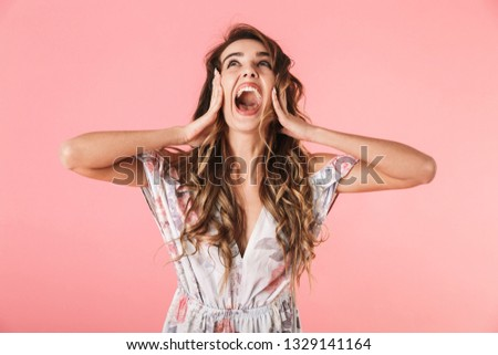 Portrait of positive woman 20s with long hair wearing dress standing and screaming, isolated over pink background #1329141164