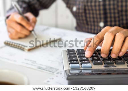 businessman hand using calculator Calculating bonus(Or other compensation) to employees to increase productivity.Writing paper on desk.Selective Focus #1329168209