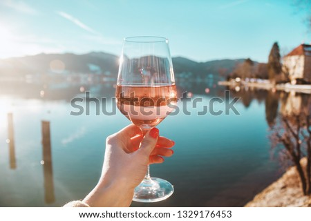 Female hand with glass of wine. Cozy pier on the coast of the lake Tegernsee. Alpine mountains in Bavaria (Bayern). Mountain view, beautiful landscape in Germany. Adventure in Europe (travel photo).  #1329176453