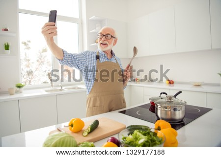 Close up photo grey haired he his him grandpa hands telephone smart phone make take pictures process cooking relatives children wear specs casual checkered plaid shirt jeans denim outfit kitchen
