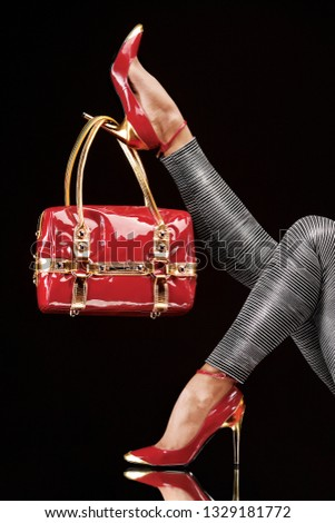 Stylish red bag hanging on a chic high-heeled shoe. Creative fashion beauty concept photo of sexy female legs wearing elegan high heels shoes and bag on black background.